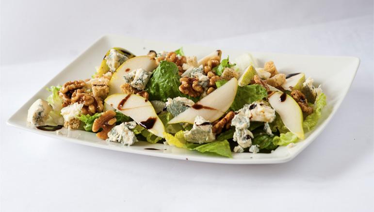 Salade avec du Cashel Blue, de la poire, des noix confites et du vinaigre balsamique